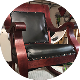 wooden chair with new leather covering the seat